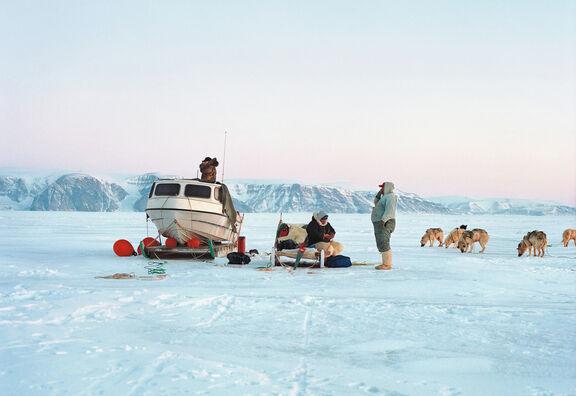 Groenlands echtpaar in de sneeuw, vrouw zit op een bank, roedel honden lopen er bij